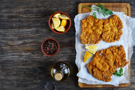 delicious golden brown two Wiener schnitzel prepared from veal slices, butterfly wing cut, served on cutting board with lemon wedges and parsley, authentic recipe, view from above, blank space left