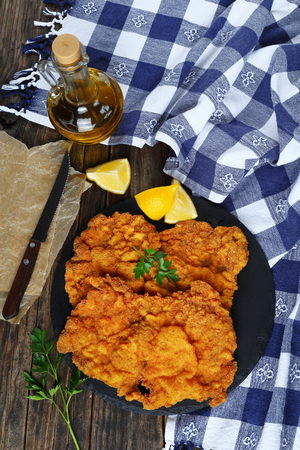 butterfly knife: delicious golden brown two Wiener schnitzel prepared from veal slices, butterfly wing cut, served on black stone plate, kitchen towel, olive oil, knife on wooden boards, vertical view from above