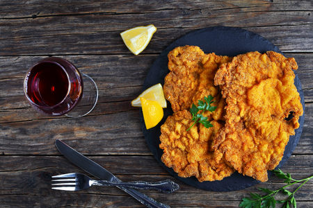 butterfly knife: delicious golden brown classic Wiener schnitzel - or breaded veal cutlets served on black stone plate with glass of red wine on dark wooden table, view from above, close-up