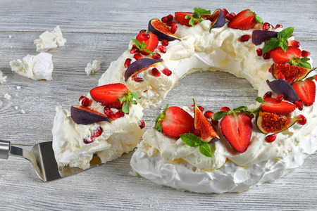 pavlova cake wreath of french meringue and whipped cream, decorated with strawberry, figs, pomegranate seeds and mint cut in slices and a piece on cake paddle, view from above, close-up