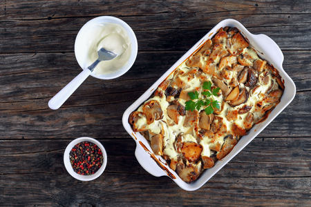 wild Mushrooms in Sour Cream Sauce in gratin dish on old wooden boards with ingredients on background, view from above Stock Photo