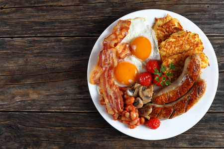 full english breakfast - bean, hash brown, fried eggs sunny side up, bacon slices, sausages, tomatoes, mushrooms on white plate on dark wooden table, view from above