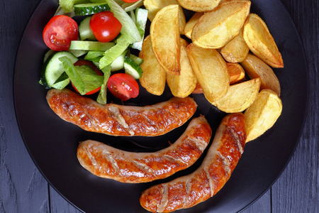 delicious hot grilled sausages, baked potatoes and fresh vegetables romaine lettuce salad on black plate on black wooden boards, view from above, close-up Stock Photo