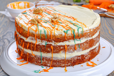 delicious classic carrot cake with cream cheese frosting decorated with walnuts and drizzled with colorful ganache on platter on wooden table with ingredients on background, view from above, close-up
