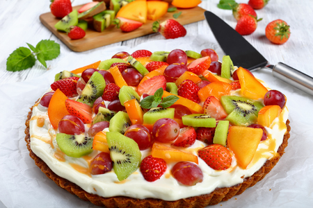 pumpkin tart with cream cheese decorated with grapes, kiwi fruit, strawberry  and persimmon, drizzled with pumpkin ganache on paper. pie lifter and cutting board on background, close-up