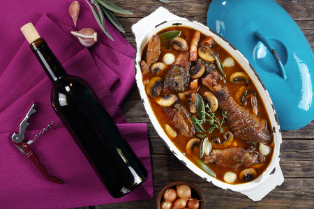 festive dinner recipe - a chicken stewed in red wine with spice, herbs, authentic french recipe - coq au vin. a bottle of wine, corkscrew, pearl onion in bowl on wooden table, view from above Stock Photo