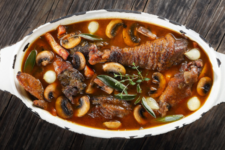 festive dinner recipe - a chicken rooster stewed in red wine with spice, herbs, authentic french recipe - coq au vin In a large oval rustic Dutch oven, view from above, close-up