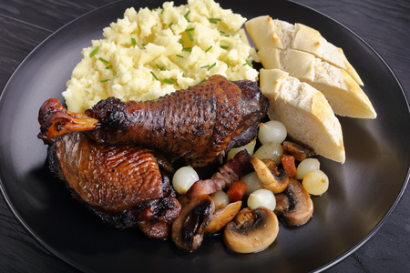 a portion of Coq Au Vin - classic French chicken stew served on black plate with potato puree and french baguette, view from above, close-up