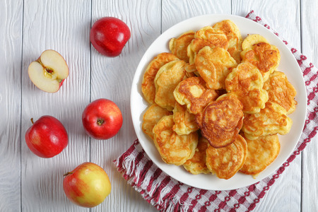 homemade Apple Greek Yogurt Pancakes - thick, fluffy and loaded with juicy pieces of fruits, on white plate with apples at background, view from above