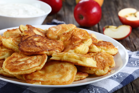 tasty fluffy Pancakes loaded with juicy pieces of apple, on white plate on old dark wooden table with sour cream in bowl and apples at background, side view from above, close-up