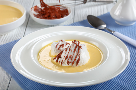 a floating island or ile flottante, consisting of meringue floating on creme anglaise and drizzled with chocolate ganache, authentic recipe, ingredients at background, view from above