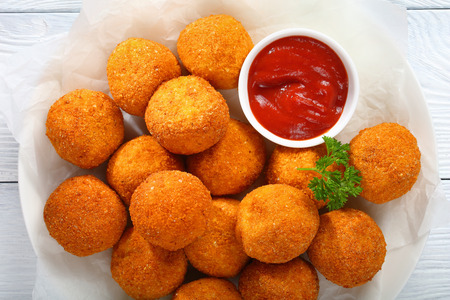 potato croquettes - mashed potatoes balls breaded and deep fried, served with tomato sauce on plate, view from above, close-up