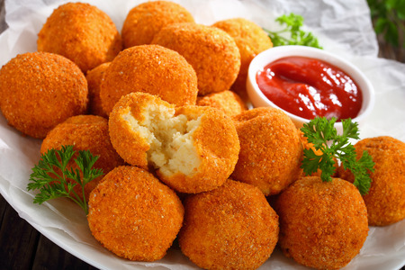 potato croquettes served with ketchup on plate and one was broken up in halves, view from above, close-up