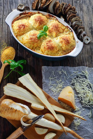 polenta vegetarian polpette stuffed with mushrooms ragout and baked in oven with parmesan cheese and parsnip sauce in baking dish. ingredients at background, vertical view from above