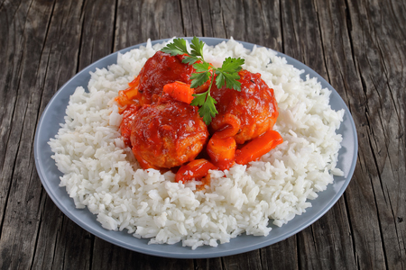 close-up of tasty hot chicken Meatball braised in tomato sauce with carrots, onion, parsnip and spices served with long grain rice on a grey plate on dark wooden table, healthy recipe, top view Stock Photo