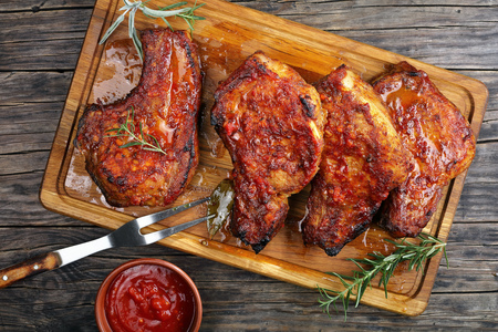 Roasted tender, juicy Pork Chops  with bay leaves, rosemary, spices on a wooden cutting board on a rustic table with barbecue sauce and fork, easy recipe for Christmas dinner, vertical view from above Foto de archivo