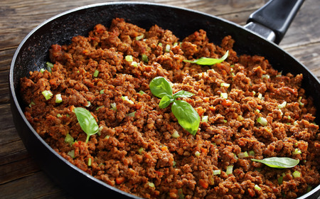 Delicious hot meat ragout bolognese with tomato sauce, finely chopped vegetables and herbs in skillet on old wooden table, classic ingredient for pasta or lasagna, view from above, close-up