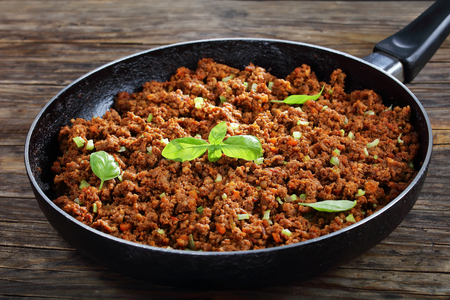 Hot juicy ground beef stewed with tomato sauce, spices, basil, finely chopped vegetables and celery in frying pan, classic recipe, side view from above, close-up