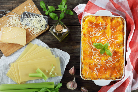 classic italian lasagna layered with bolognese ragout, topped with melted cheese and fresh basil leaves in baking dish. ingredients for lasagna at background, view from above, close-up