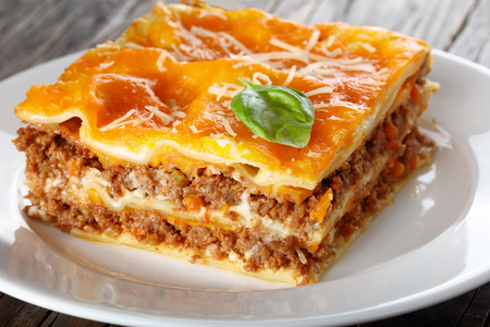 close-up of a portion of delicious italian lasagna topped with melted cheese and fresh basil leaves, sprinkled with grated parmesan cheese on white plate, traditional recipe