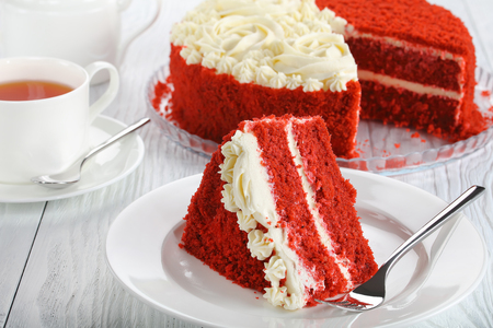 a slice of red velvet cake topped with beautiful creamy roses on white dish on table with cup of tea and cake at background,  side view from above, close-up Stockfoto