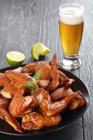delicious crispy smoked chicken wings on a black stone plate on wooden table with foamed fresh beer in a glass and lime slices, vertical view from above, close-up