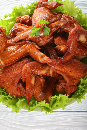 delicious crispy smoked chicken wings on lettuce pad on a white plate on wooden kitchen table, view from above