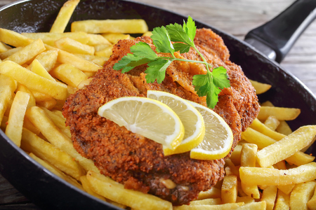 delicious Cutlet Cordon Bleu with French fries, parsley and lemon slices in skillet on old dark wooden table, side view from above, close-up 스톡 콘텐츠