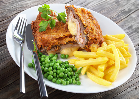 delicious Cordon Bleu with French fries, green peas and parsley on plate on old dark wooden table with silver fork and knife, authentic recipe, close-up