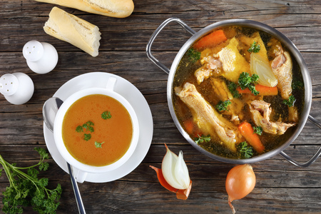 clear Chicken broth with pieces of rooster meat on bone and vegetables in a metal casserole and in a soup cup on dark wooden table, view from above, close-up Foto de archivo