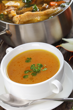 delicious Chicken broth with pieces of chicken meat on bone and vegetables in a metal casserole and in a soup cup on dark wooden table, vertical view from above, close-up