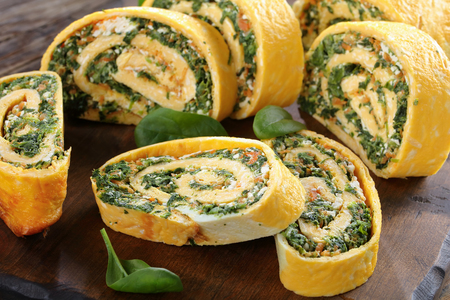 delicious egg roulade made from a flat piece of savoury sponge, spread with a soft filling of spinach, feta and carrots and rolled up into a spiral, view from above, close-up
