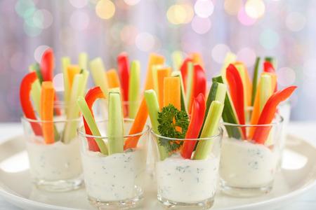 Apéritif de verrines avec carotte, concombre, céleri et poivron rouge bâtons dans des verres sur un plateau à fond bokeh, vue d'en haut, gros plan