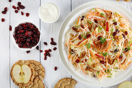 close-up of Apple Cranberry and walnuts Coleslaw salad on a white plate on wooden table with red apple slices, multigrain crispbread, yogurt sauce and nuts at background, view from above