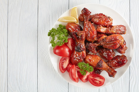 tasty grilled crispy juicy teriyaki chicken drumsticks sprinkled with sesame seeds on white plate with tomatoes, parsley and lemon slices, view from above