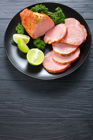 delicious ham cut in slices served with parsley and fresh citrus wedges on black plate on black wooden table, vertical view from above