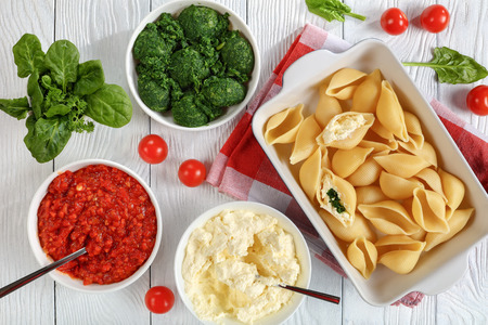 big pasta shells in the making to be stuffed with cheese and spinach. sauce marinara, fresh spinach leaves, soft cheese mixed with grated mozzarella in bowl on wooden table, view from above Foto de archivo