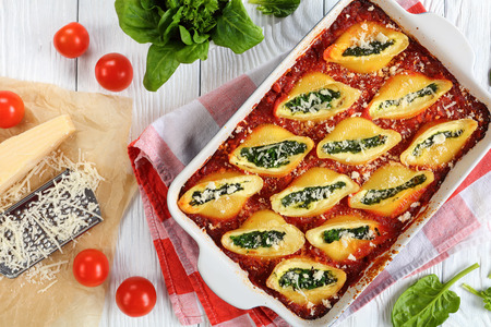 delicious big pasta baked shells stuffed with creamy soft cheese and spinach sprinkled with parmesan cheese in baking dish. grated parmesan cheese on paper, italian recipe, view from above, close-up