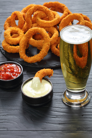 delicious golden breaded and deep fried crispy onion rings served on round black stone tray on black wooden table with sauces, glass of foamed beer at background, vertical view from above Stock Photo