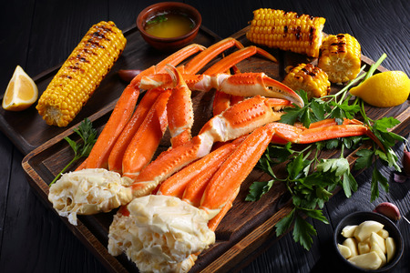 snow Crab legs served with melted butter, garlic cloves, lemon slices, grilled corn in cobs and fresh parsley on wooden cutting boards, horizontal view from above, close-up