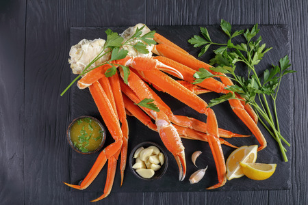 cooked Crab legs with melted butter sauce, garlic and fresh parsley on black stone tray, on wooden table, view from above Stock Photo