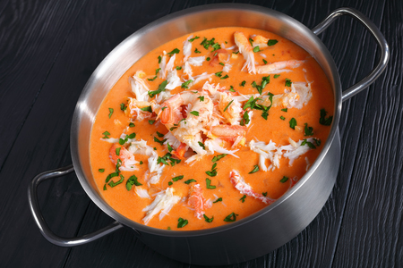close-up of savory delicious hot bisque or thick soup of shredded snow crab meat, prawn, lobster in a stainless metal casserole on black wooden table, authentic french recipe, view from above Foto de archivo