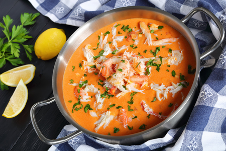 delicious hot bisque or thick soup of shredded snow crab meat, prawn, lobster in a stainless metal casserole on black wooden table with kitchen towel and lemon, view from above, close-up
