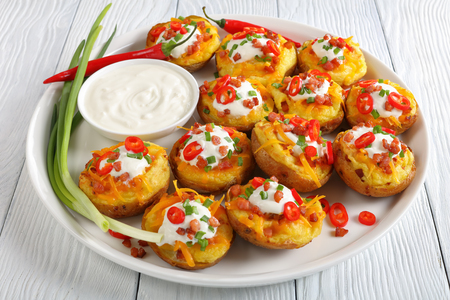 delicious baked potato halves loaded with grated cheddar cheese, bacon, chili peppers slices, sour cream on white platter with sour cream in bowl, view from above, close-up