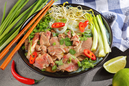 Vietnamese soup Pho Bo with rice noodle, raw sirloin beef slices, bean sprouts, lime, spring onion in black bowl with chopsticks and ingredients on concrete table, close-up