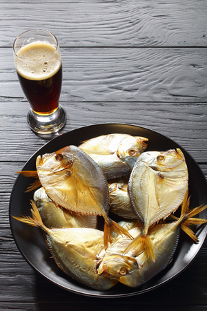delicious cold smoked moon fish on black plate and  glass of foamed dark beer on black wooden table, view from above