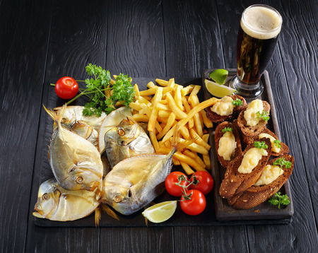 delicious cold smoked moon fish and french fries served on a black stone tray with capelin caviar crispy toasts and glass of foamed dark beer, view from above, close-up Stock Photo
