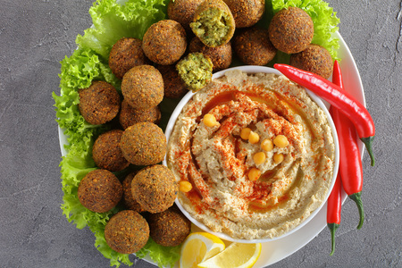 close-up of delicious falafel balls on plate with hummus in a bowl, chili peppers and lettuce leaves, classic recipe, horizontal view from above Stock Photo