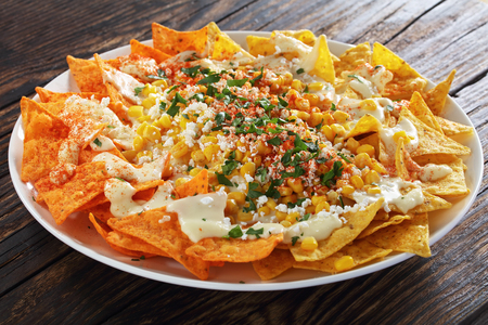 close-up of crunchy nachos or Tortilla chips topped a creamy cheese sauce, toasted corn kernels, crumbled cheese, chili powder and cilantro served on platter, view from above Banco de Imagens
