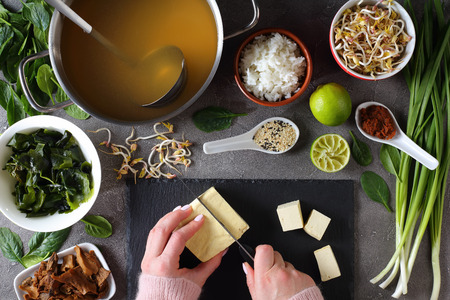 woman is cutting tofu into cubes for traditional japanese miso soup. dashi, miso paste, wakame seaweeds, steamed rice, mushrooms, greens and spices at concrete background, view from above